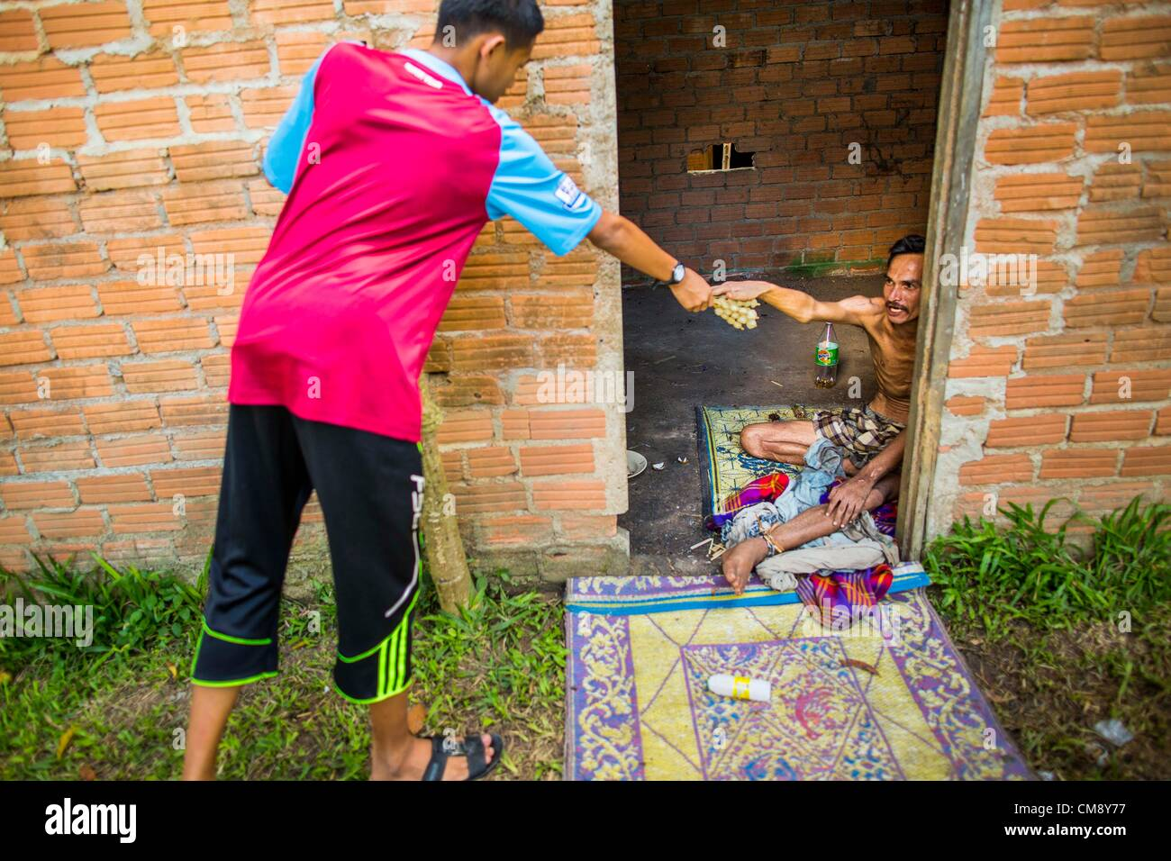 Ottobre 29, 2012 - Mayo, Pattani, Tailandia - un quartiere ragazzo porta il cibo per un paziente presso il Bukit Immagini Stock