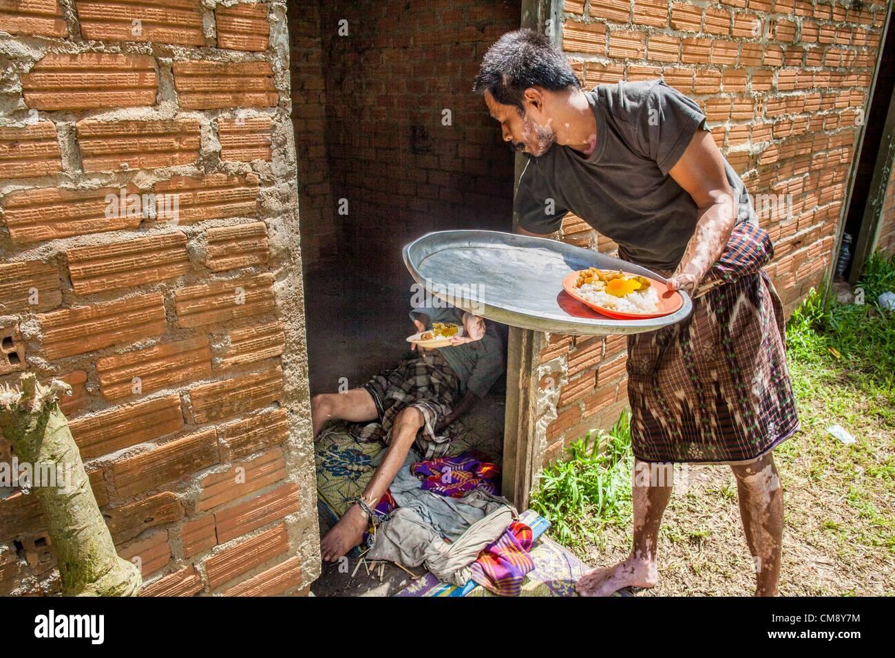 Ottobre 29, 2012 - Mayo, Pattani, Tailandia - un fiduciario porta il cibo per un ammanettato residente presso il Immagini Stock