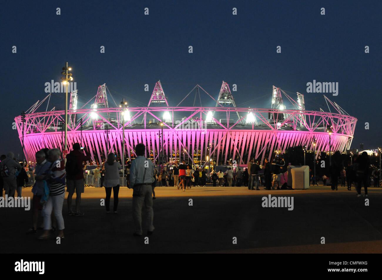 Gli spettatori si riuniscono per fotografare i campi illuminati da 2012 Athletics Stadium come tramonto cade nel Immagini Stock