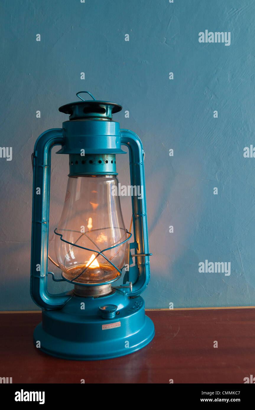 Illuminato in vecchio stile di cherosene/lampada ad olio su tavola con sfondo blu Immagini Stock