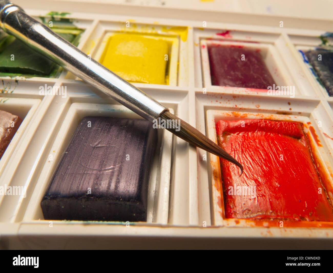 Primo piano della spazzola in bilico sopra compressa di rosso il colore dell'acqua in una scatola di vernice. Immagini Stock