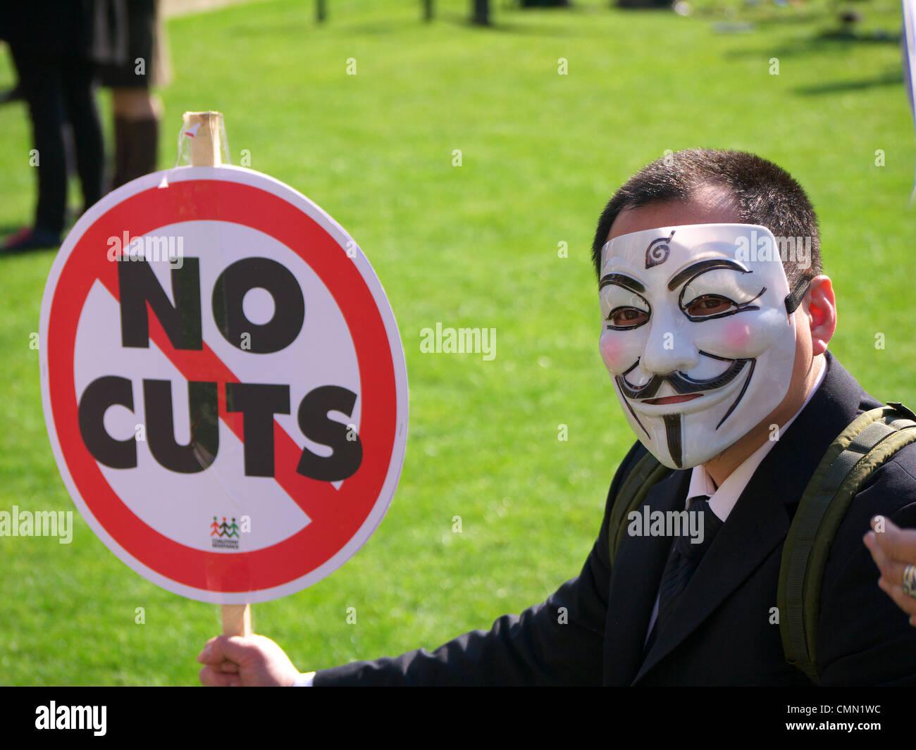 Un anonimo protester indossare una maschera tenendo un 'No tagli' segno di protesta a un bilancio giorno Immagini Stock