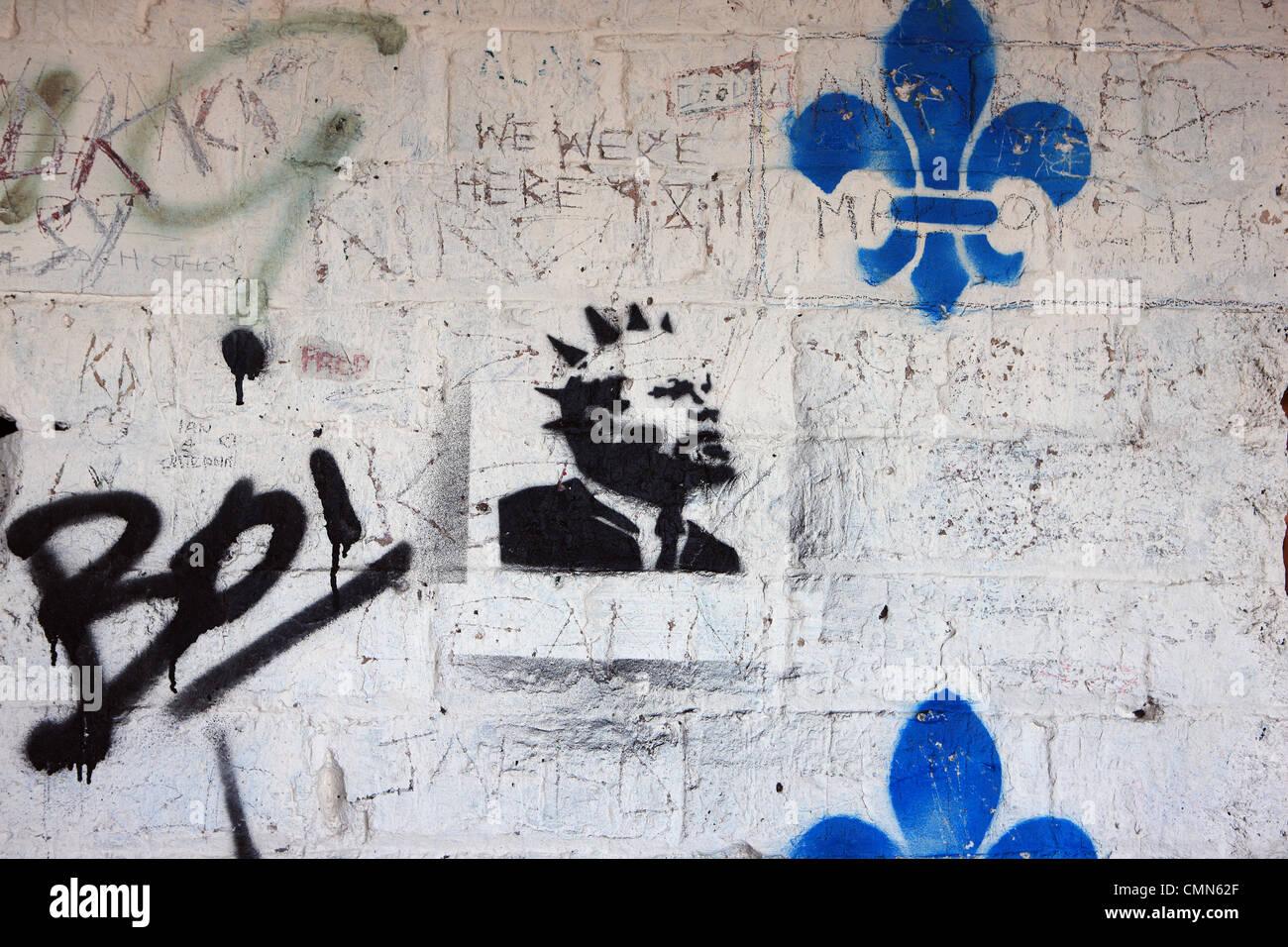 Graffiti e la tecnica a stencil sul muro di un edificio abbandonato Immagini Stock