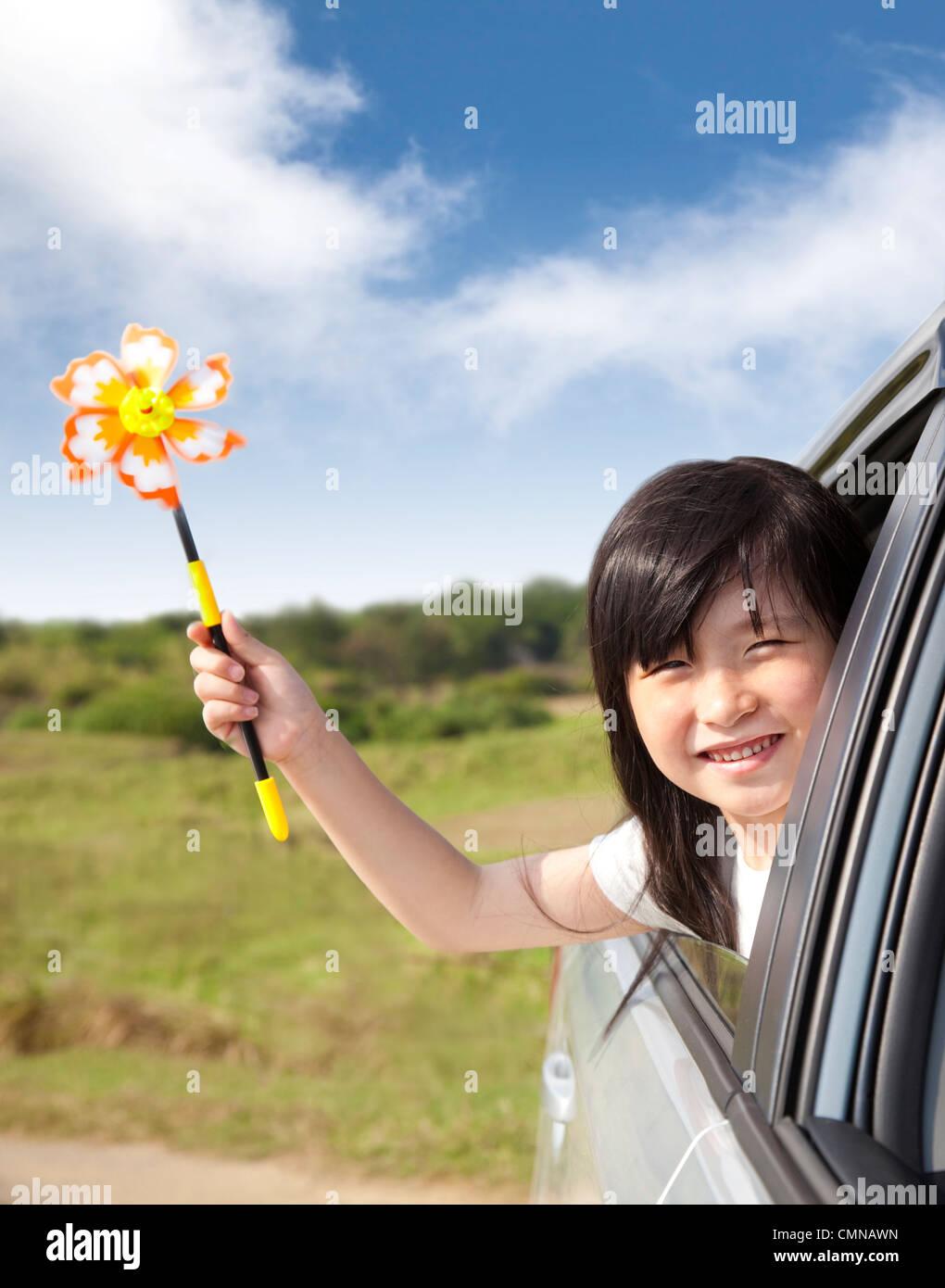 Piccolo felice ragazza con il mulino a vento in auto Immagini Stock