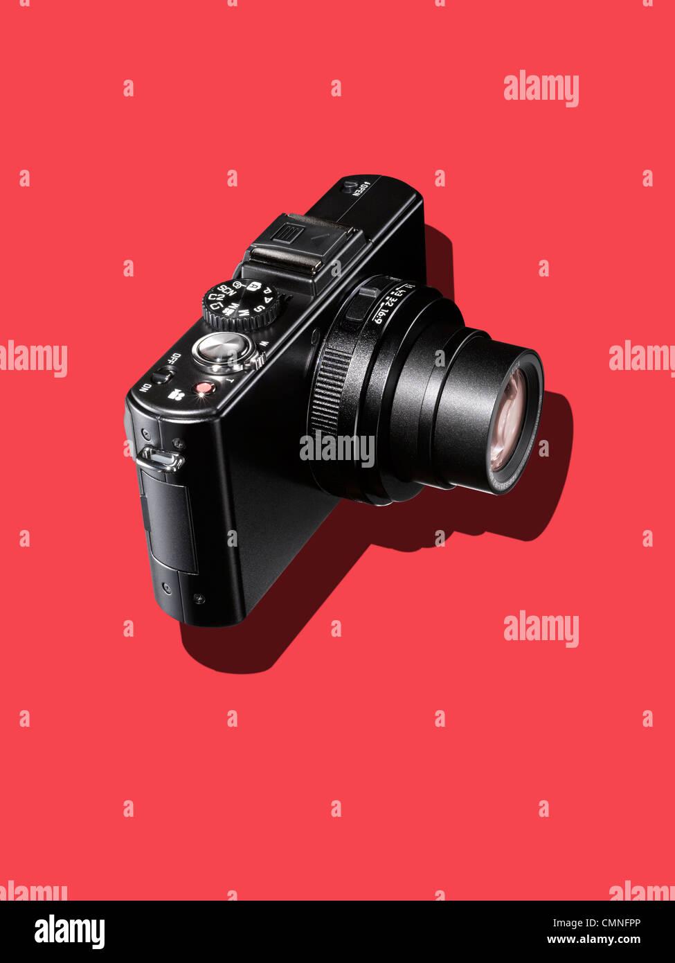 Una fotocamera nero su uno sfondo rosso Immagini Stock