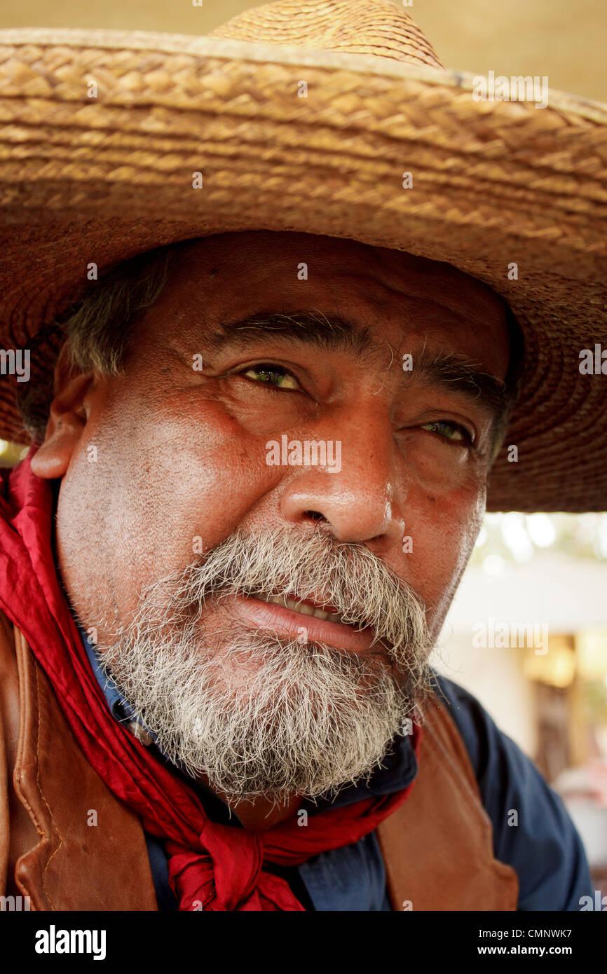 Ritratto di vecchio cowboy con barba grigia e cappello di paglia lo sguardo  all orizzonte. 28ff6a439421