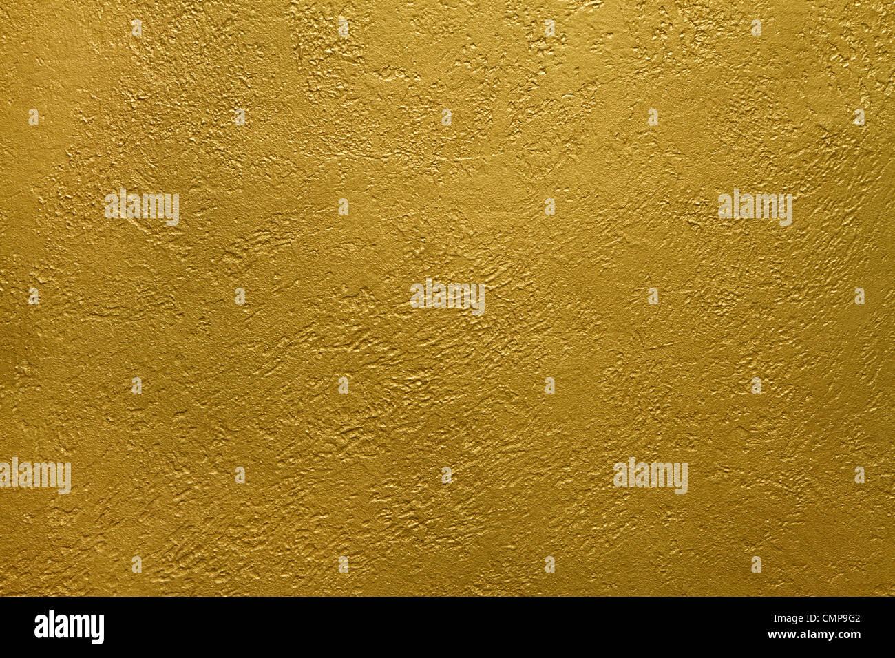 La texture di un muro di cemento rivestito con vernice dorata Immagini Stock