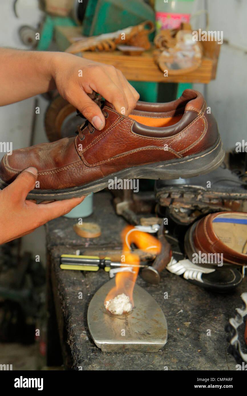 Lima Peru Barranco Avenida Pierola shoe repair business negozio cobbler uomo ispanico strumento commerciale workbench Immagini Stock