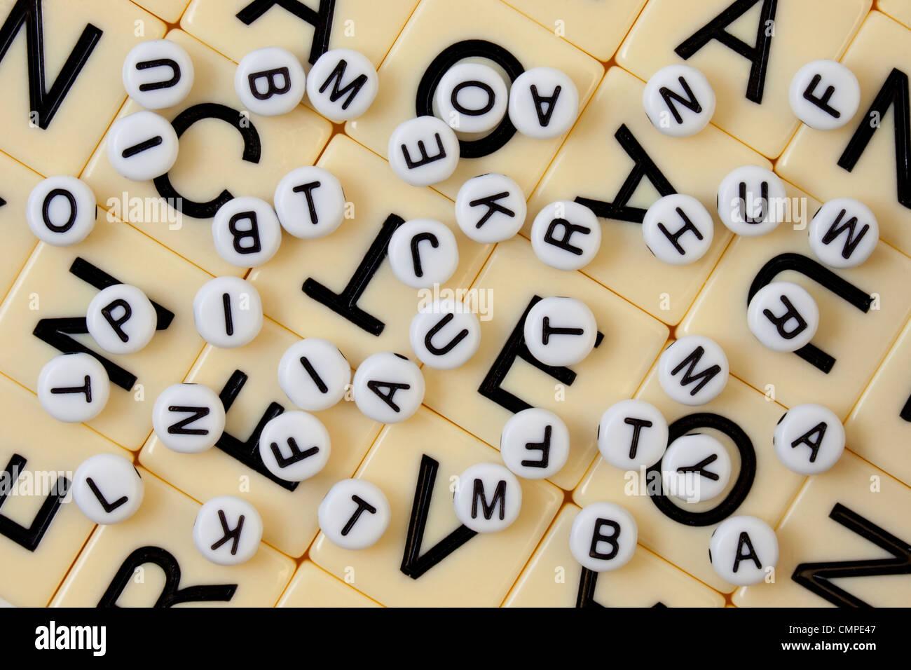 Perle bianche con lettere in nero rovesciato in maniera casuale su un mosaico di avorio con lettere più grandi Immagini Stock
