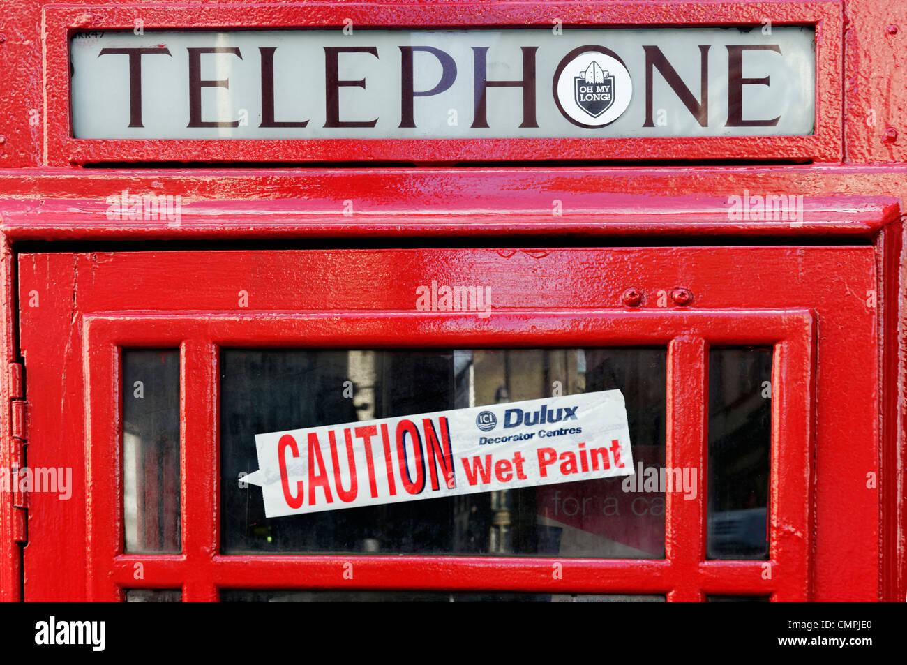 Un rosso telefono pubblico booth con un 'attenzione - vernice fresca' etichetta nella finestra Immagini Stock