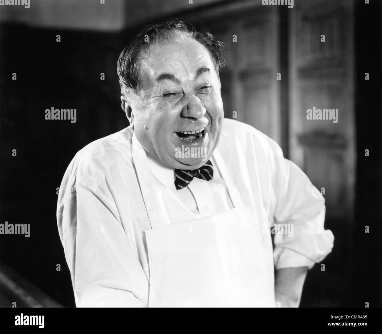 1930s 1940s Laughing Man ritratto indossando il grembiule macellaio BAKER DROGHERIA CLERK SERVICE uomo felice Immagini Stock