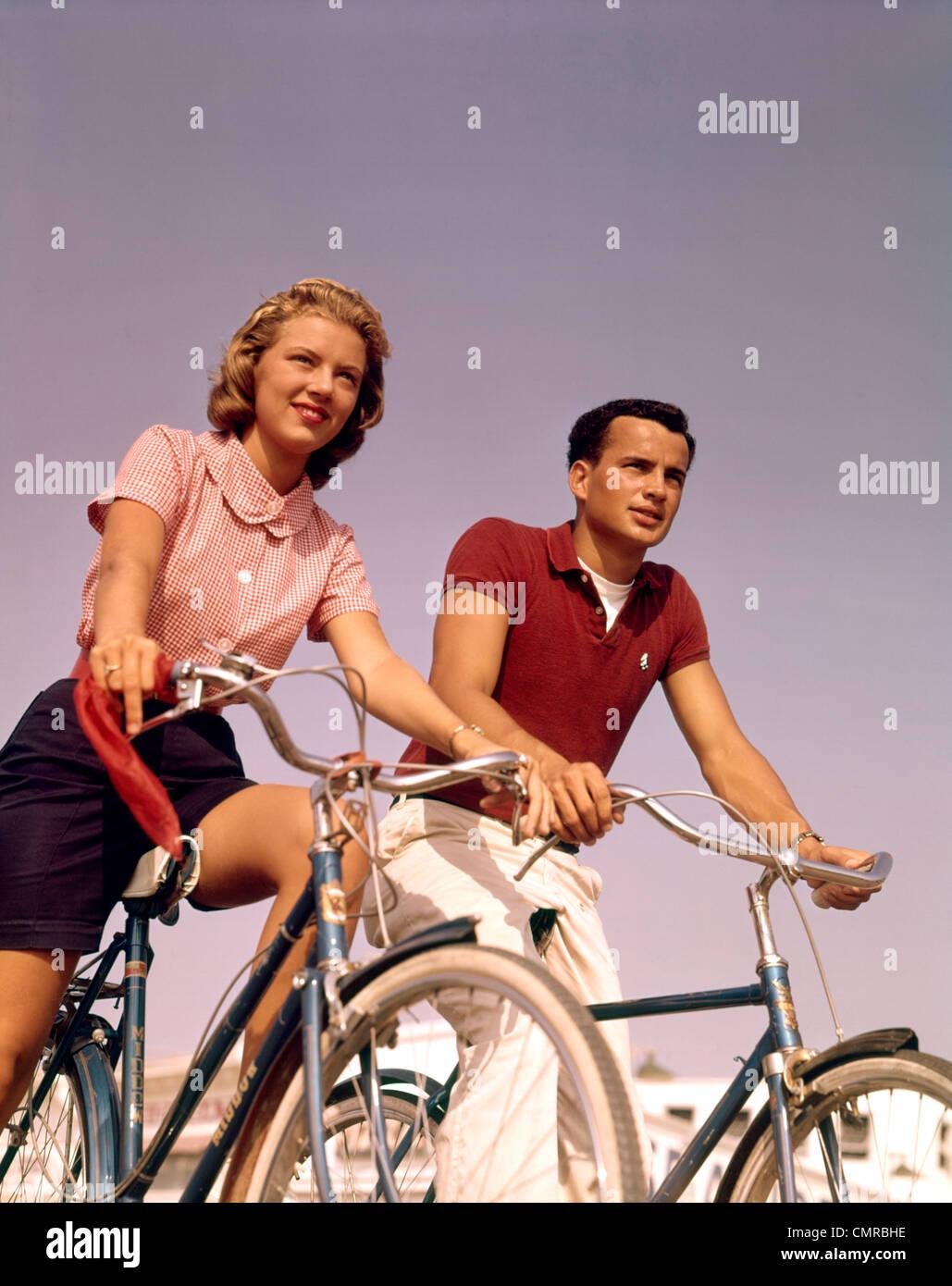 Anni Cinquanta anni sessanta GIOVANE UOMO DONNA equitazione biciclette all'aperto Immagini Stock