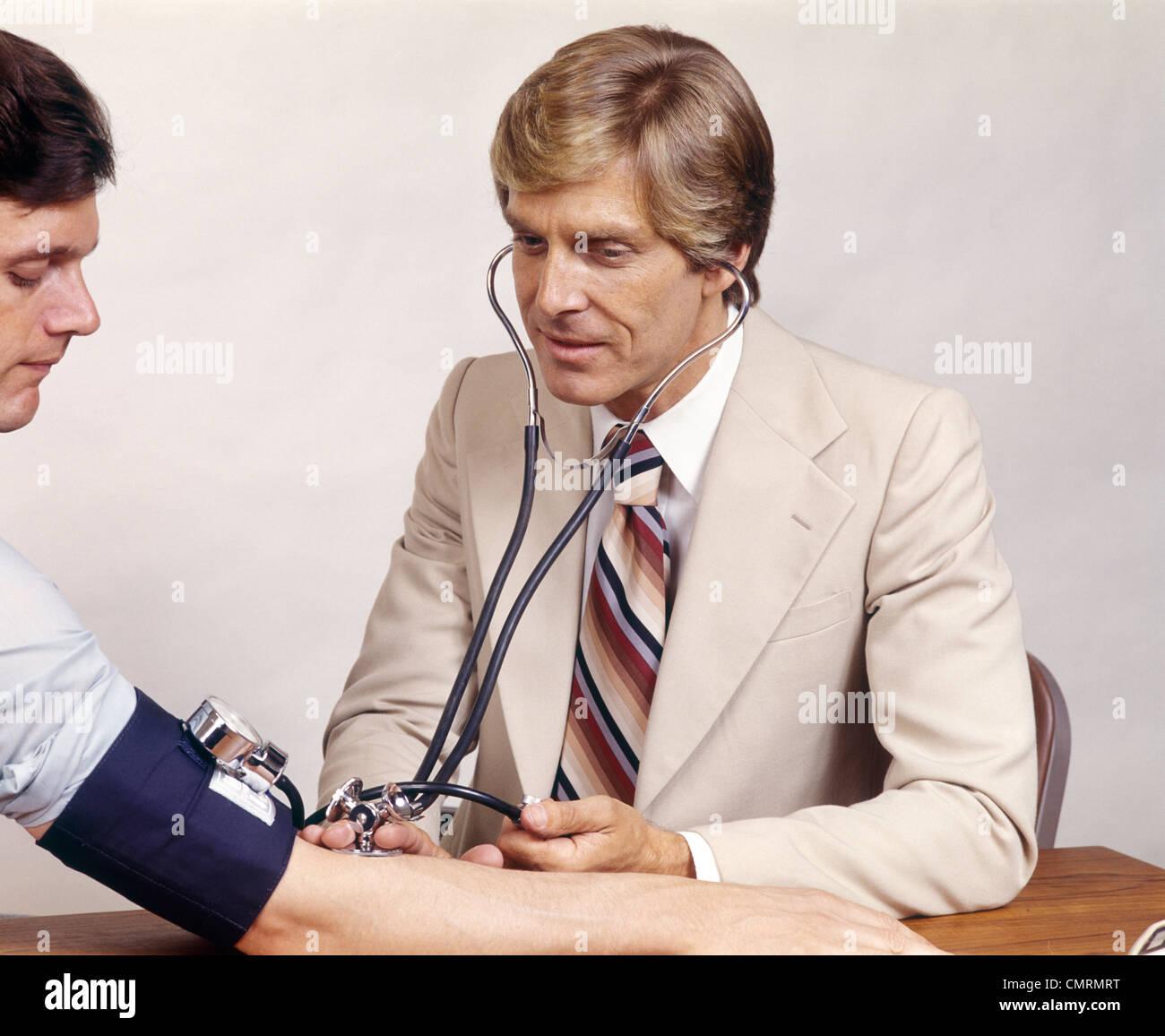 1970 anni settanta retrò uomo medico utilizzando uno stetoscopio per controllare la pressione del sangue del paziente Foto Stock
