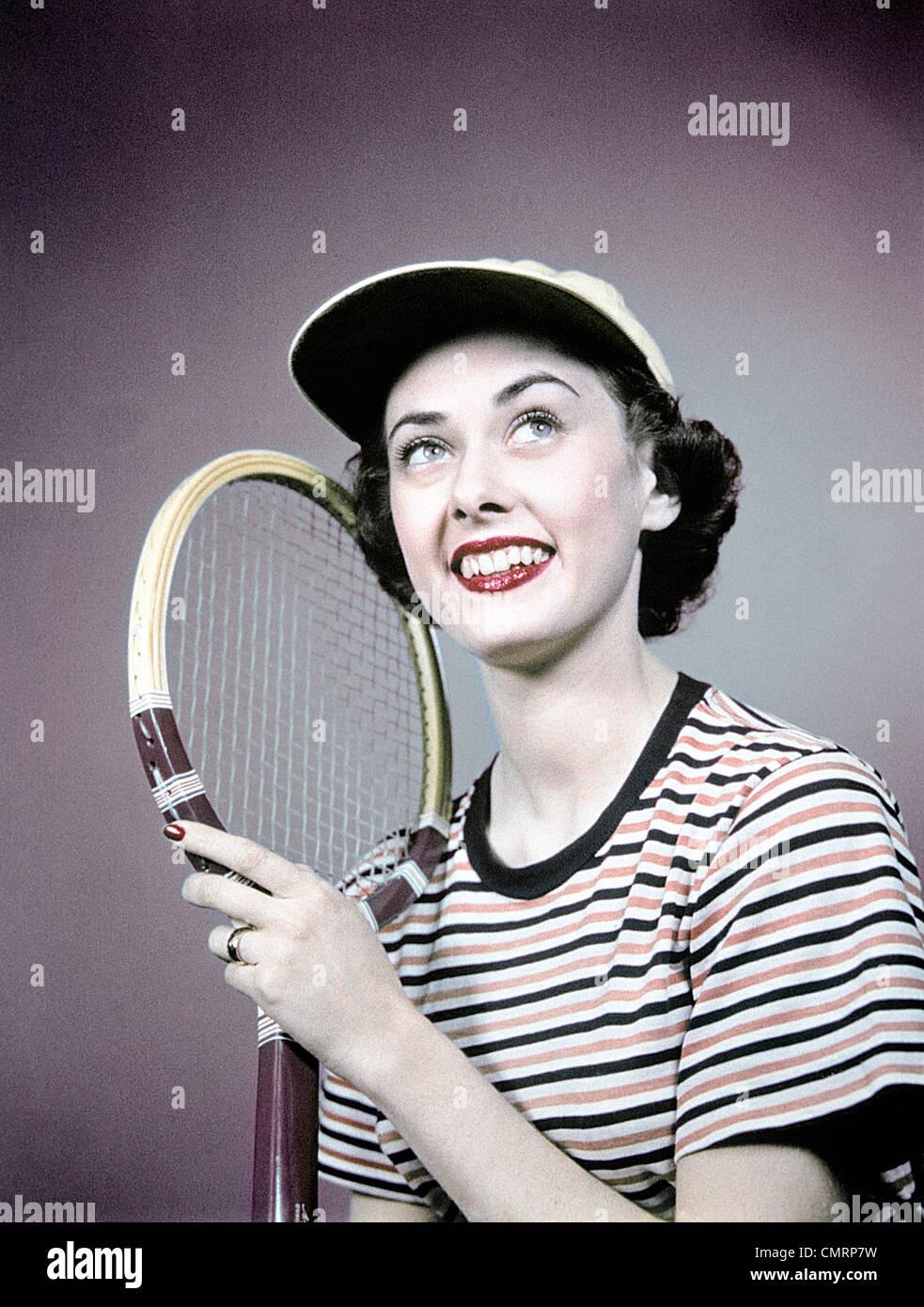 Anni Cinquanta sorridente BRUNETTE DONNA HOLDING racchetta da tennis Wear Camicia a Righe CAP Immagini Stock