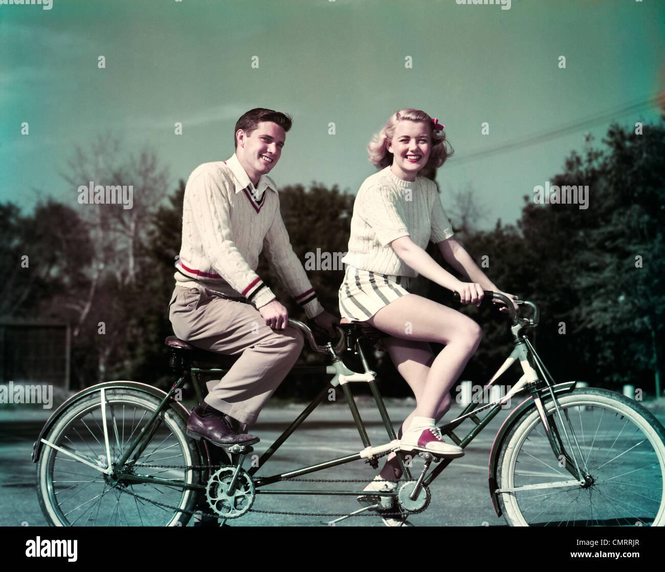 Anni Cinquanta sorridente giovane equitazione biciclette tandem costruita per due Foto Stock