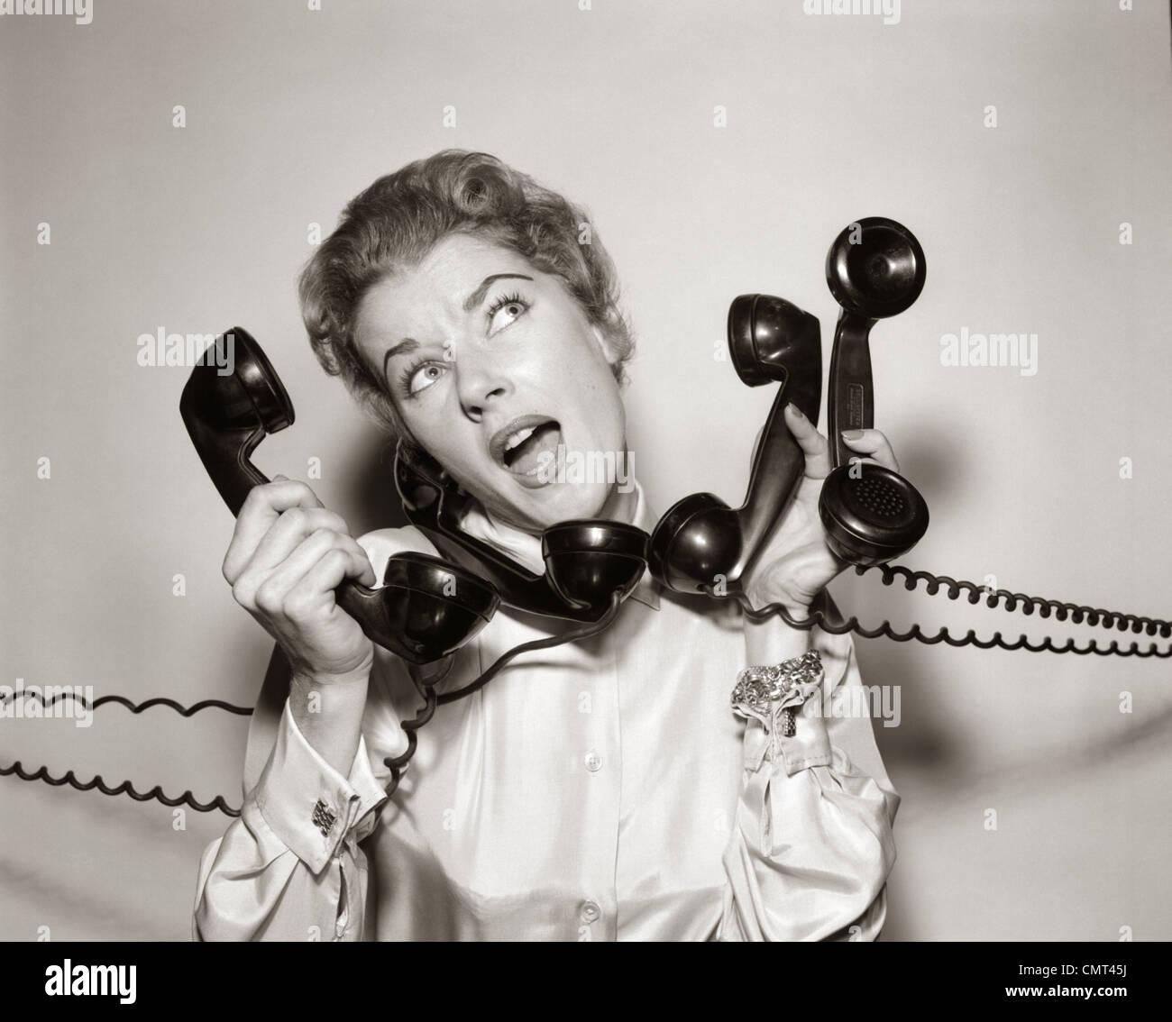 Anni Cinquanta anni sessanta sopraffatto sottolineato donna azienda rispondendo alle quattro telefonico nero i ricevitori Immagini Stock