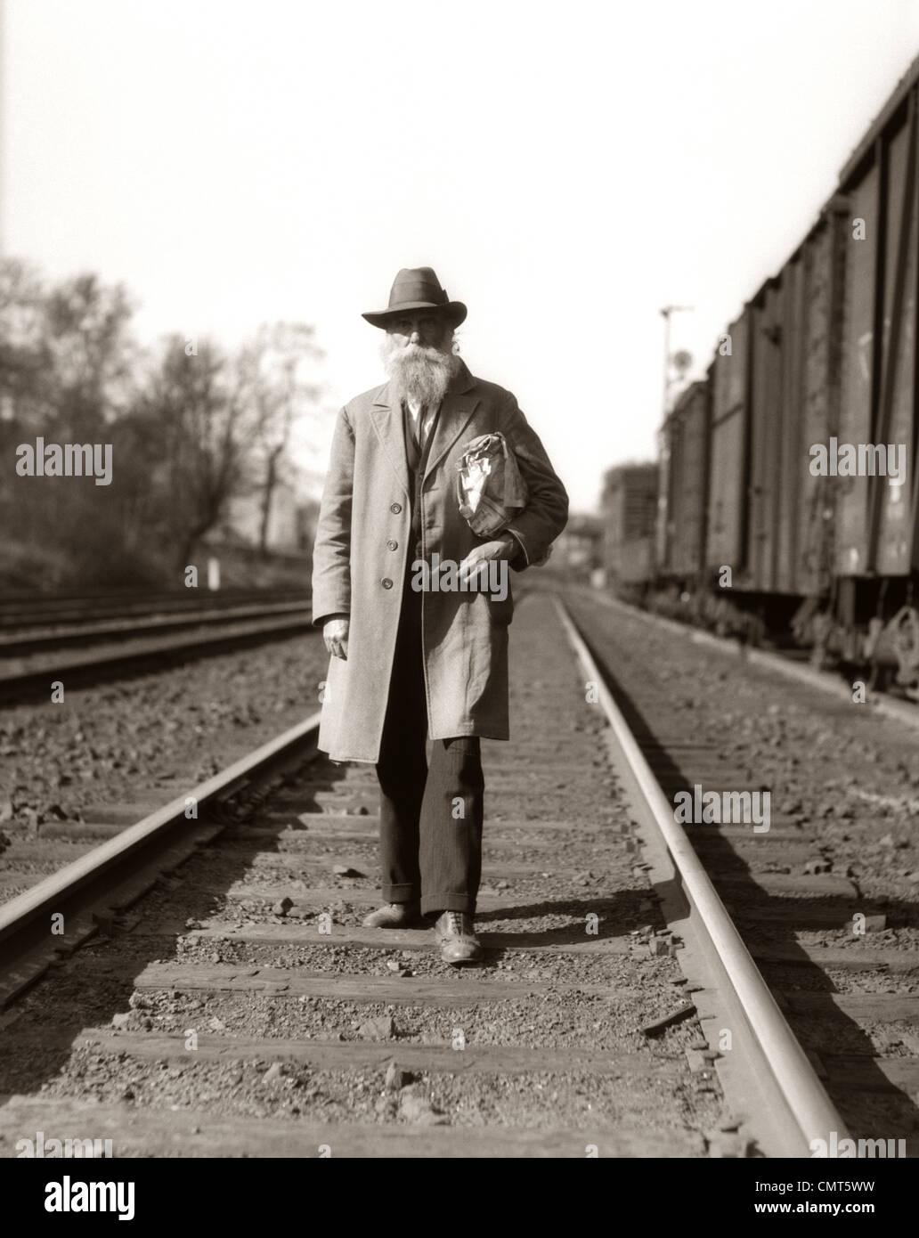 1930s grande depressione era uomo senzatetto HOBO percorrendo a piedi i binari della ferrovia Immagini Stock