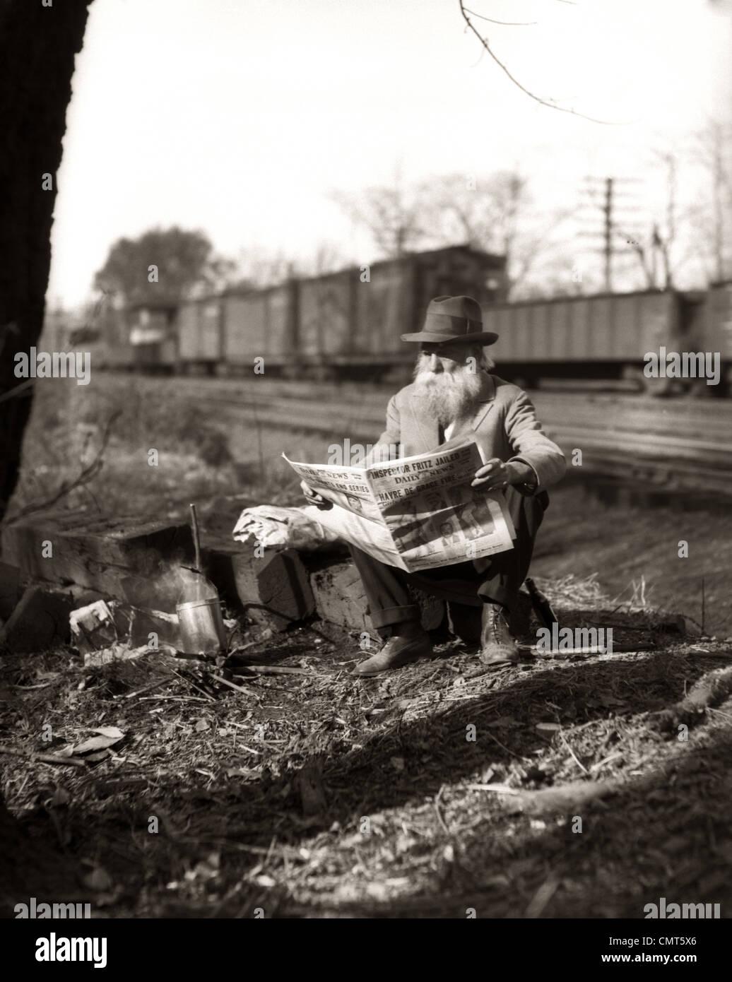 1930s HOBO SEDUTA DA ferrovia via quotidiano di lettura durante la Grande Depressione Immagini Stock