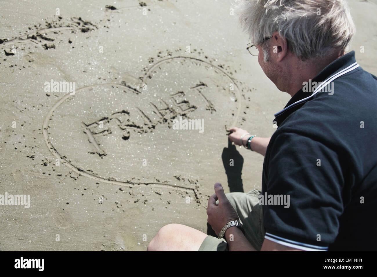 Elevato angolo di visione dell'uomo cuore di disegno sulla sabbia Immagini Stock