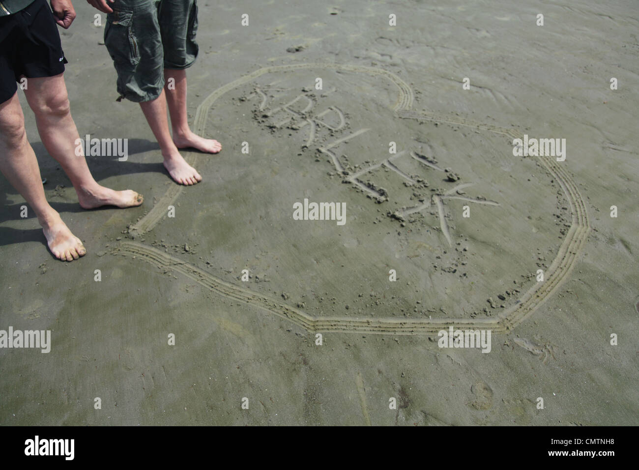 Angolo di alta vista di gambe umane e il cuore sulla spiaggia Immagini Stock
