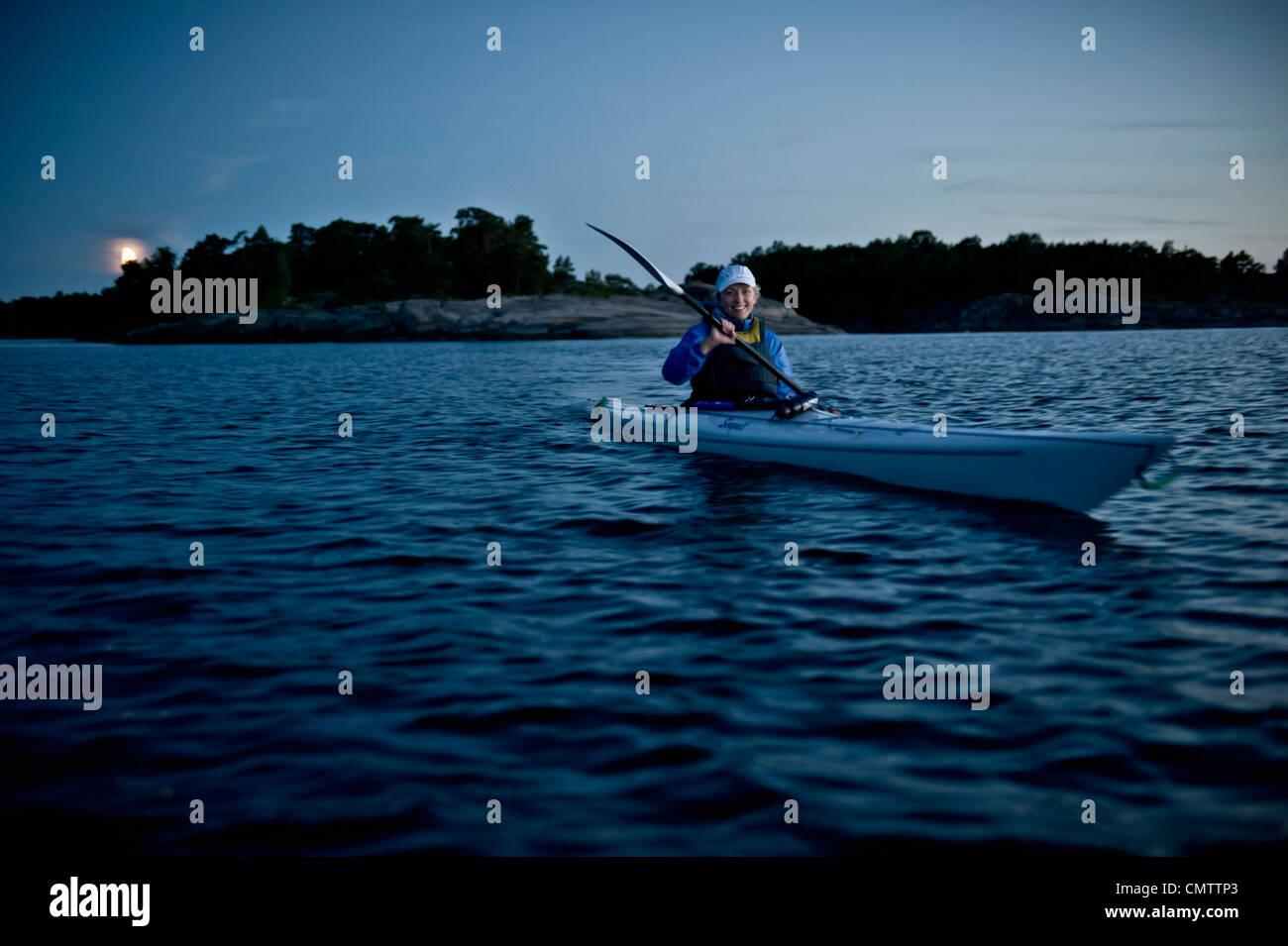 Donna sorridente nel recipiente nautico oaring Immagini Stock