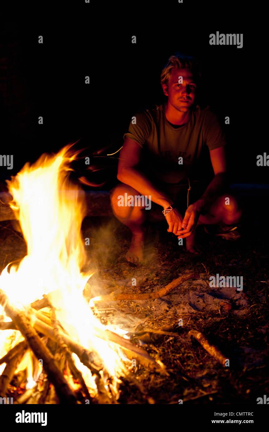 Uomo seduto accanto al fuoco Immagini Stock
