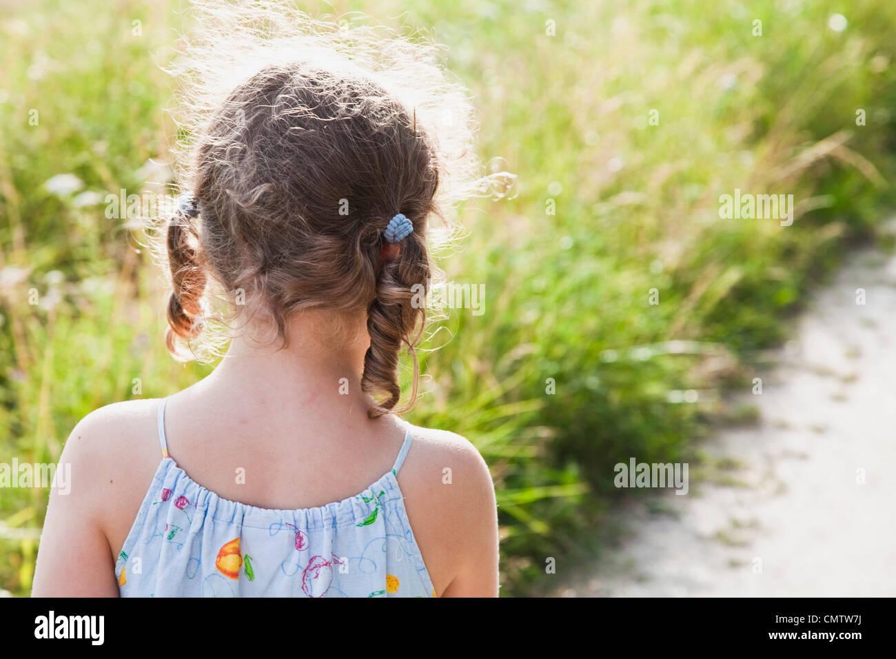 Vista posteriore di una ragazza contro erba Immagini Stock