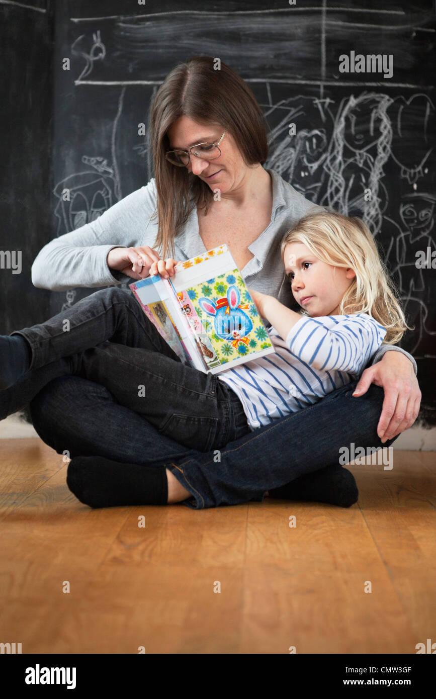 Madre aiutare la propria figlia in studi Immagini Stock
