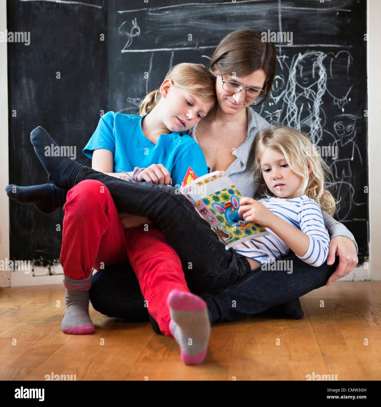 Madre aiutare le sue figlie in studi Immagini Stock