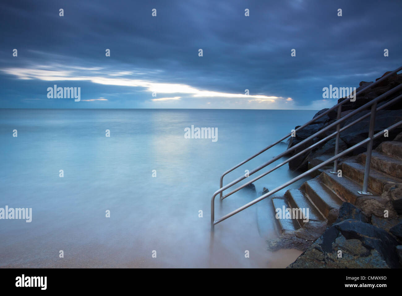 Lavaggio onde su gradini che conduce al mare. Machans Beach, Cairns, Queensland, Australia Foto Stock