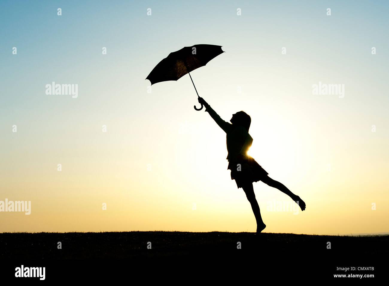 Ragazza giovane jumping con un ombrello al tramonto. Silhouette Immagini Stock