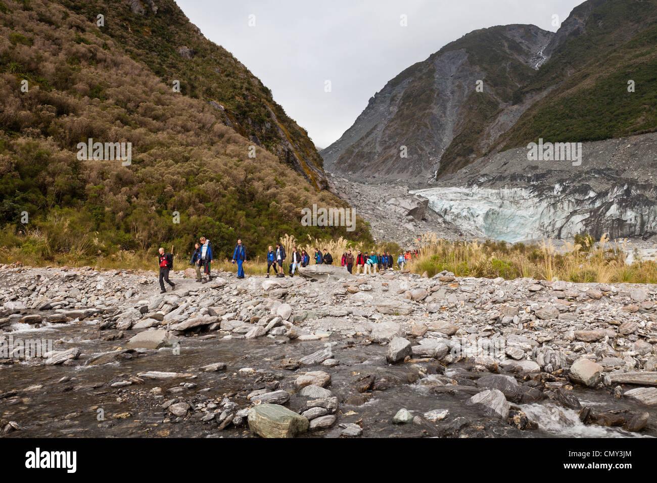 Partito guidato dei turisti che lasciano il terminale del ghiacciaio Fox, nella costa occidentale della Nuova Zelanda. Immagini Stock