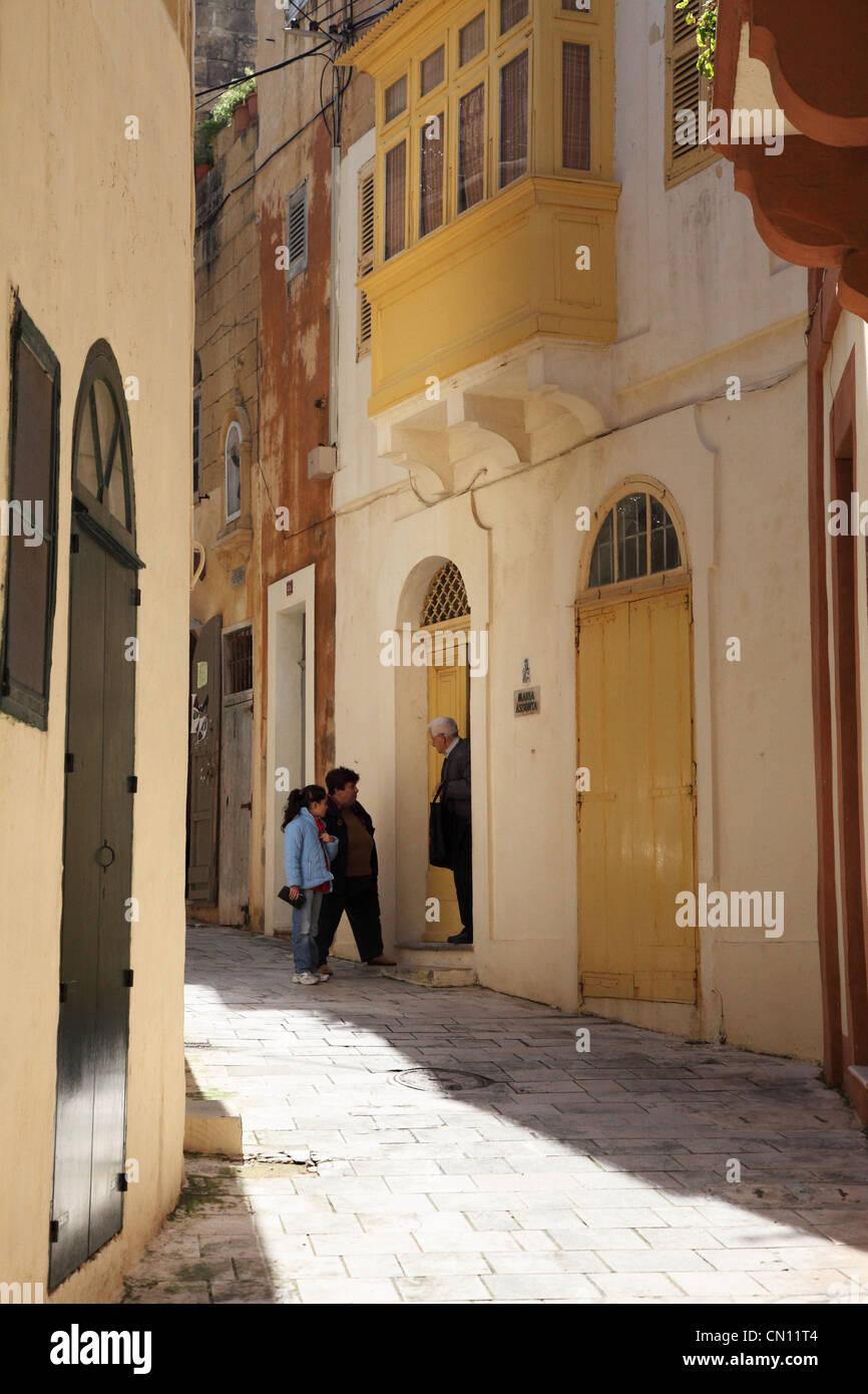 Tre persone di Gozo entro un vicolo sul Mediterraneo isola di Gozo vicino a Malta in Europa Immagini Stock