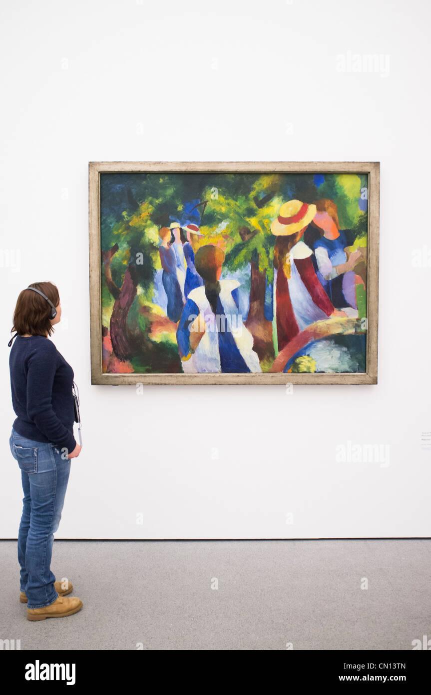 Donna che guarda la pittura Madchen unter den Baumen da August Macke a Pinakothek Moderne Art Museum di Monaco di Immagini Stock