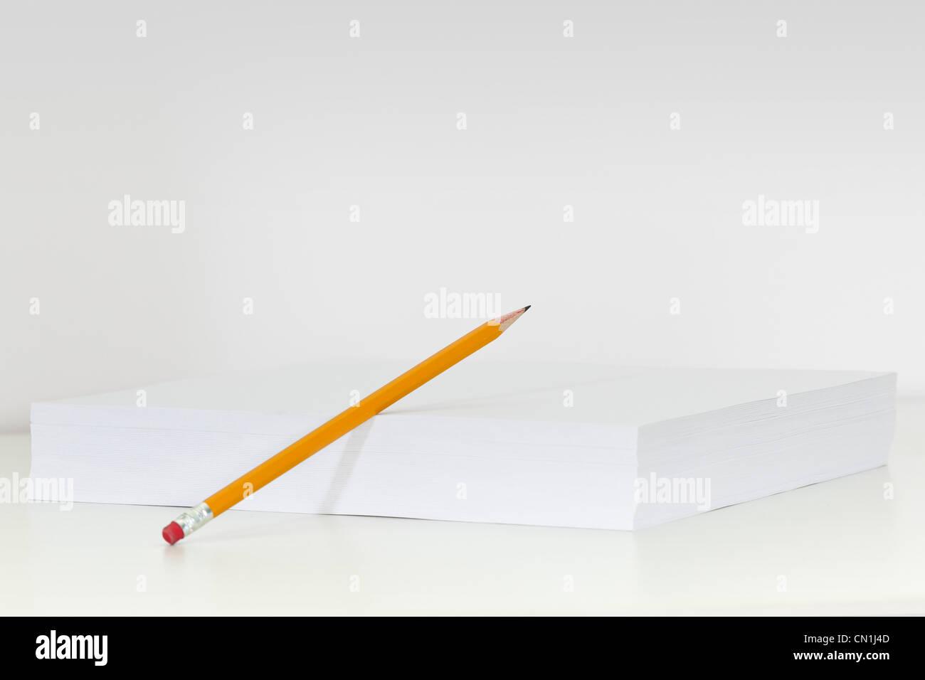 Matita appoggiata contro la pila di carta bianca Immagini Stock