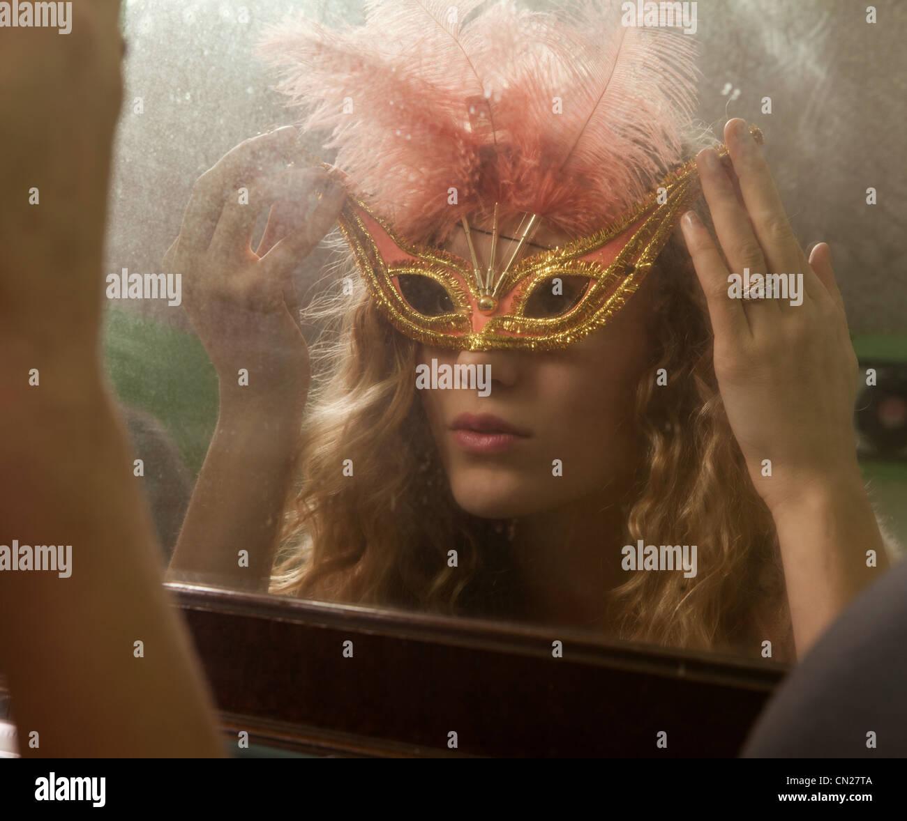 Ragazza adolescente indossando masquerade mask nella parte anteriore dello specchio Immagini Stock