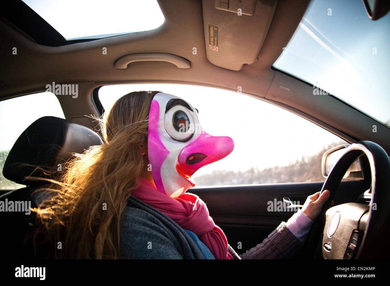 Donna alla guida di auto indossando maschera clown Foto Stock