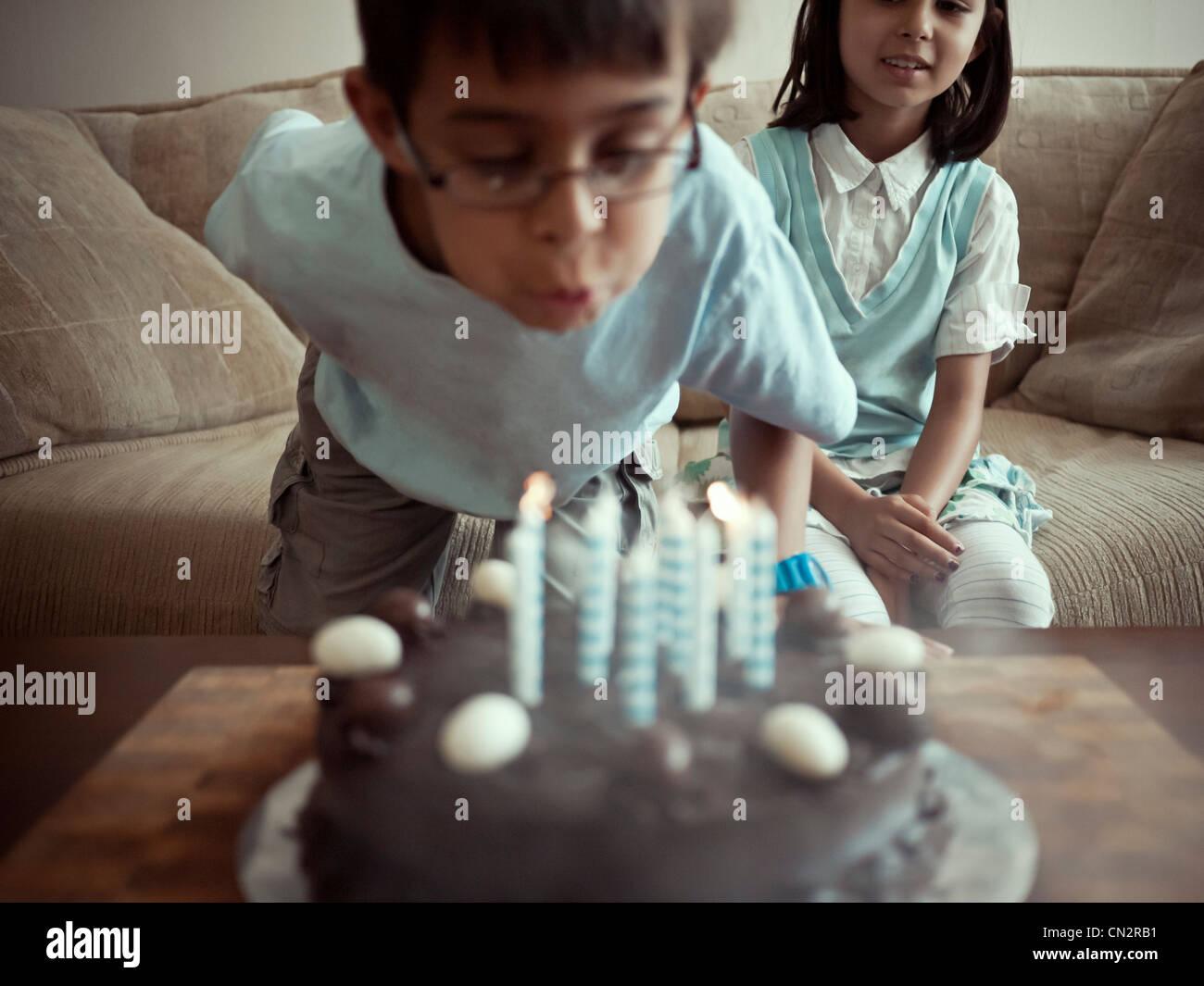 Che spegne le candeline sulla torta del compleanno Immagini Stock