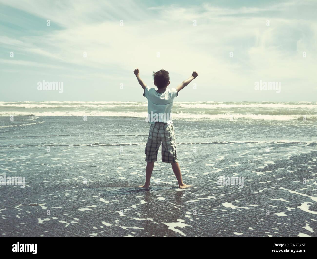 Ho premuto indietro il mare: ragazzo sulla spiaggia, Nuova Zelanda. Immagini Stock