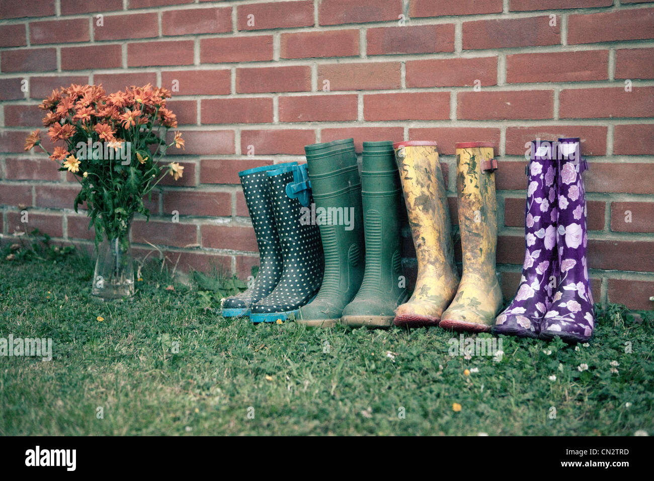 Stivali da pioggia da un muro di mattoni Immagini Stock