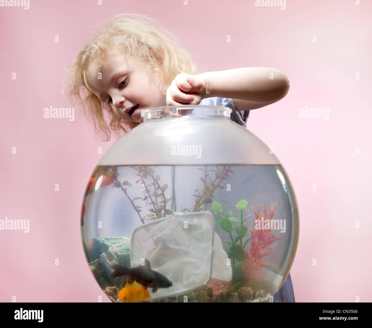 Ragazza giovane con la rete da pesca e Goldfish Bowl Foto Stock