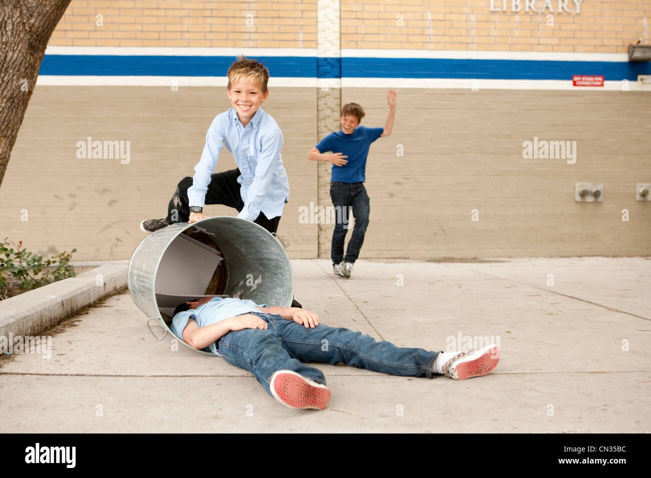 Due ragazzi il bullismo un altro, un ragazzo nel bidone della spazzatura Immagini Stock