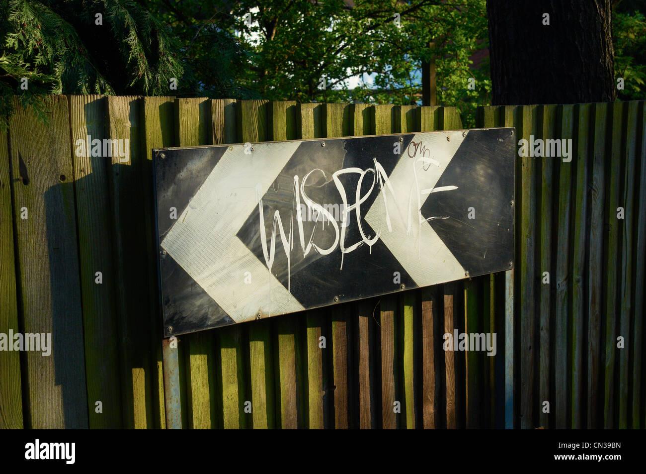 Graffiti sul cartello stradale sulla recinzione Immagini Stock