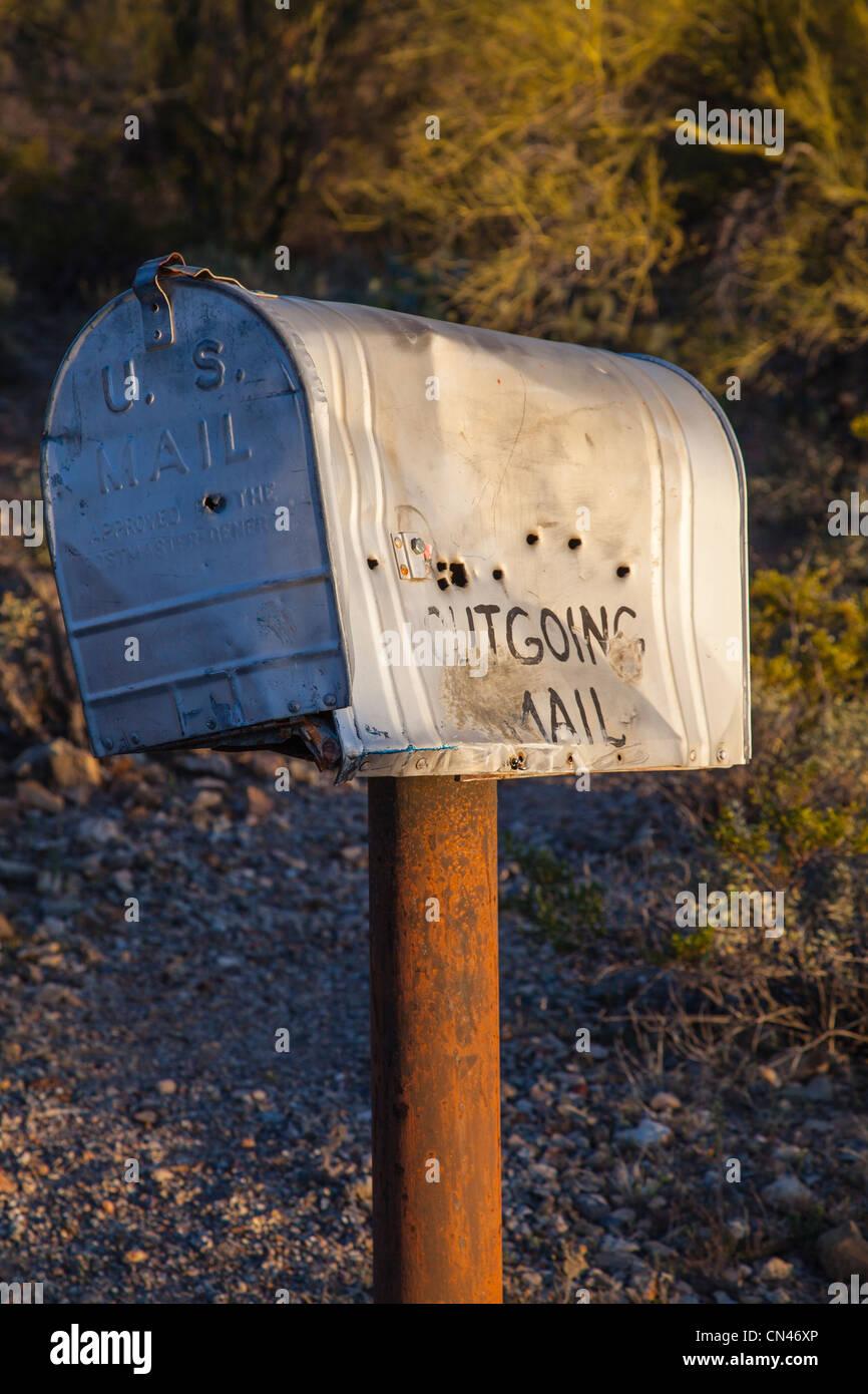 Cassetta postale rurale nel deserto con fori di proiettile e 'Posta in uscita' scritto su di esso. Foto Stock