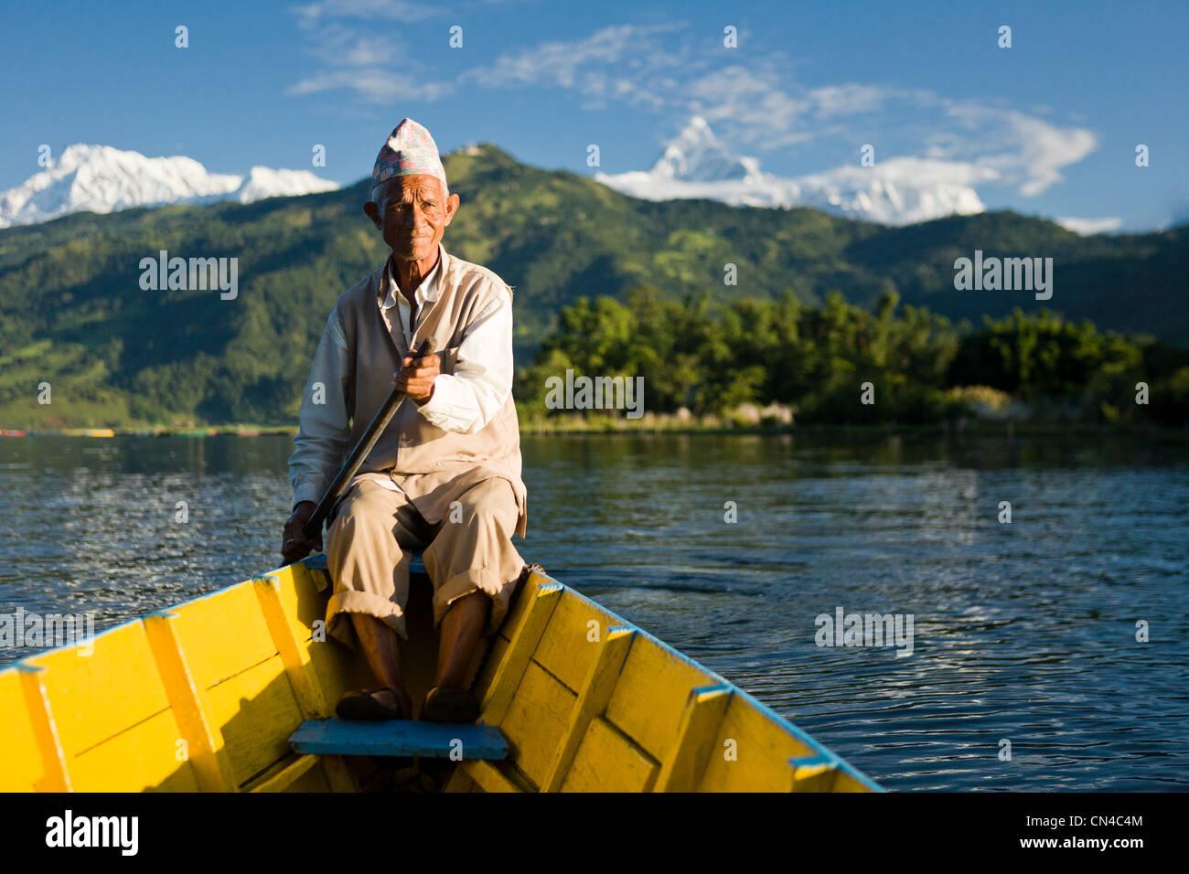 Uomo nepalese a remi in barca tradizionale Immagini Stock