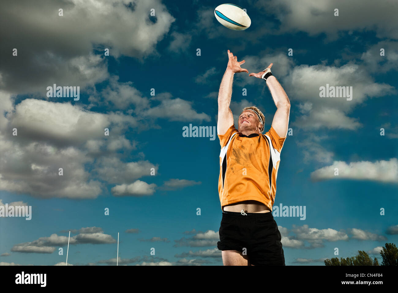 Giocatore di rugby che saltava fino alla sfera di cattura Immagini Stock