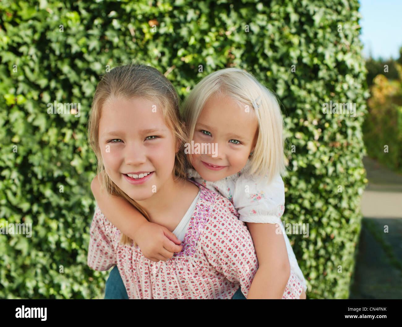 Ragazza portati dalla sorella sul retro, sorridente, ritratto Immagini Stock