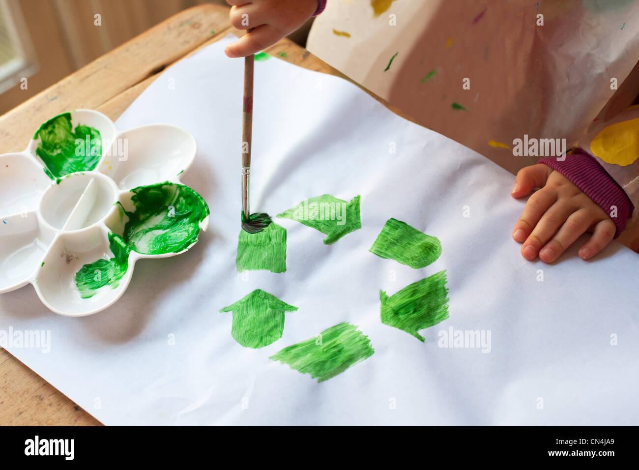Bambino pittura verde simbolo di riciclaggio Immagini Stock