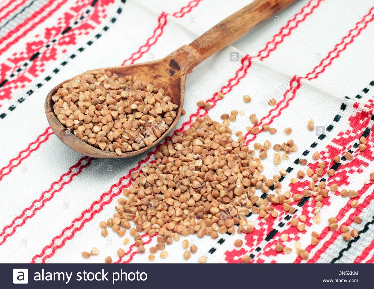 Il grano saraceno in cucchiaio di legno sul tessuto bianco Immagini Stock
