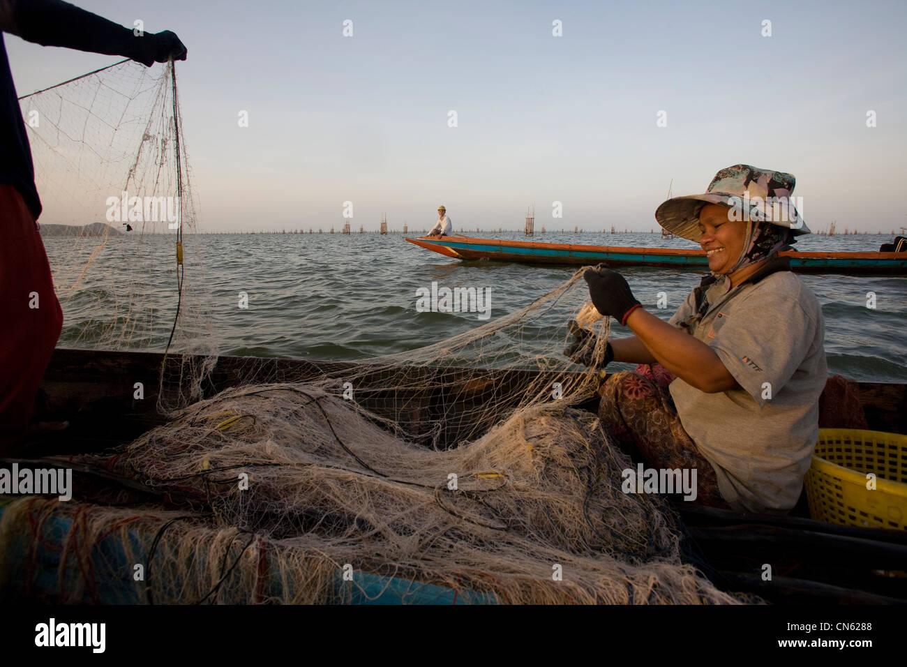 I pescatori e le donne all'alba di raccogliere le loro catture dalle reti e gabbie cadere sul letto di Songkhla Immagini Stock